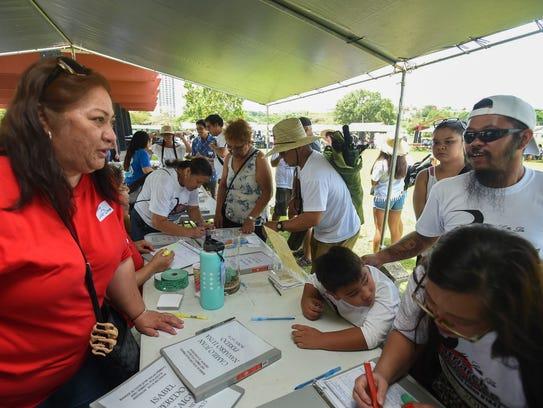 Catalino Blas Peredo relatives sign in during the Peredo