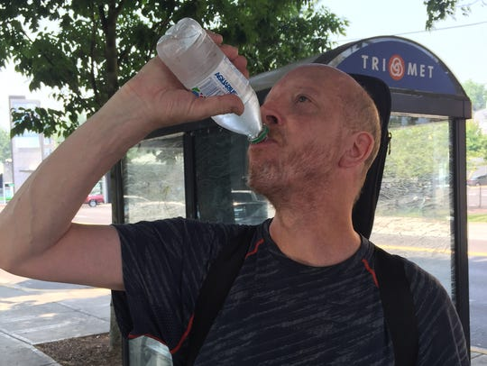 Jeff Kennedy drinks bottled water after passing a Salvation