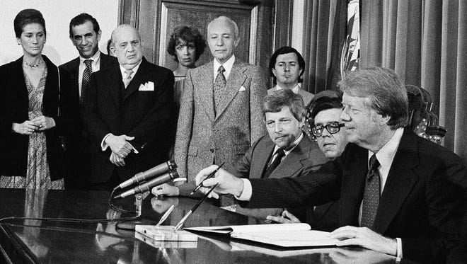 In this June 1, 1977 file photo, President Jimmy Carter prepares to sign the American Convention on Human Rights at the Pan American Building, in Washington. From left are: Chile Amb. Maria Eugenia Oyarzun; unidentified aide; Nicaraguan Amb. Guillermo Sevilla-Sacasa; Patricia Derian, U.S. Women's Rights coordinator; Paraguay Amb. Marion Lopez Escobar; Marcelo Huergo, OAS staff; Gale McGee, U.S. ambassador to the OAS; Juan Pablo Gomez, OAS council chairman; Carter; and Alejandro Orfila, OAS secretary general (not pictured). Derian, who actively supported Mississippi public school desegregation and served as assistant secretary of state for human rights during the Carter administration, has died. Derian's son, Michael Derian, confirmed his mother died early Friday, May 20, 2016. She was 86.