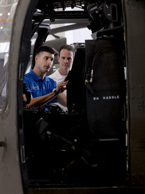 In this 2015 LSJ file photo, state Rep. Tom Barrett, left, shows Kevin Cotter, then speaker of the State House, the controls inside a UH-60 Blackhawk helicopter. The Michigan National Guard has cleared Barrett of any wrongdoing in an Oct. 6, 2017 helicopter landing at Perry High School.
