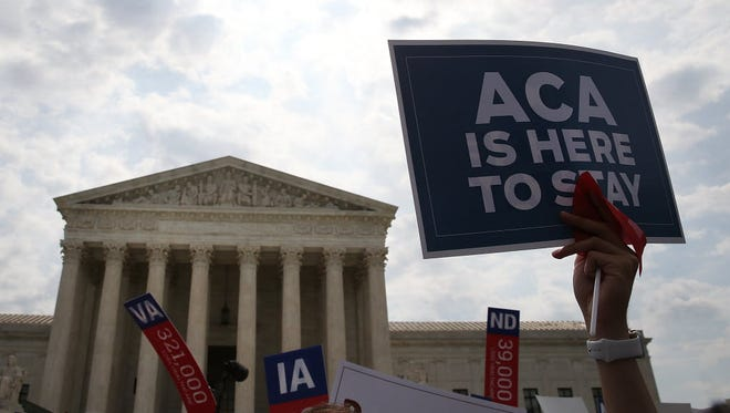 "A sign is held up that reads ""ACA Is Here To Stay"" front of the US Supreme Court after ruling was announced in favor of the Affordable Care Act. June 25, 2015 in Washington, DC."