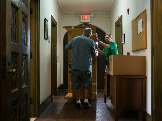 Maintenance boss Pablo Gonzalez (left) and volunteer Marty Kirk removes a desk from a room to give space for a freezer at Christ Our King church food closet which hopes to remain open after the sale of the church.