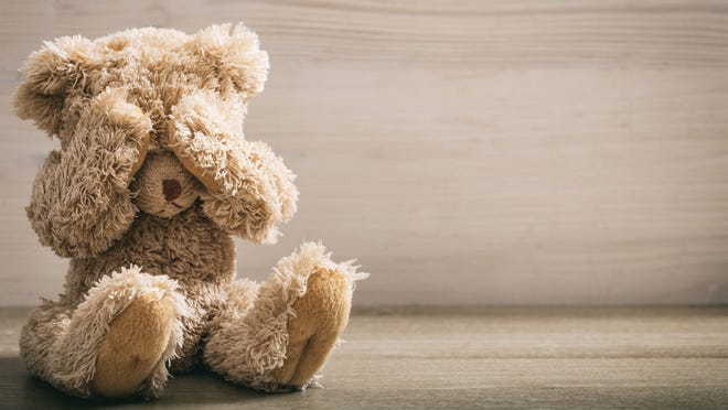 Frightened teddy bear covers its eyes