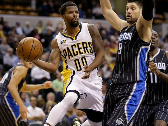 Aaron Brooks (00), facing Orlando Magic center Nikola