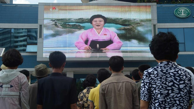 Residents watch a big video screen on Mirae Scientists Street in Pyongyang showing newsreader Ri Chun-Hee as she announces the news that the country has successfully tested a hydrogen bomb on Sunday.