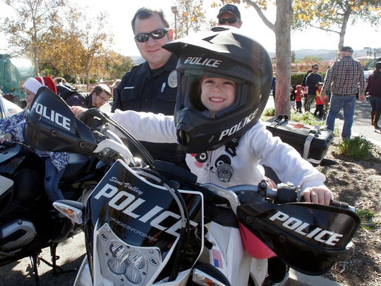 Simi Valley police officer Joe Pesce, of the off-road enforcement team, watches as Emmalyn Woodward enjoys a moment on his motorcycle during the fourth annual Touch-a-Truck family event in Simi Valley on Saturday.