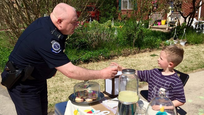 Ulysses Stoutenburg, 5, of Spring Garden Township, serves lemonade to Spring Garden Township Police Officer Jacob Clevenger. Ulysses set up a lemonade stand May 2, to raise money for York County libraries.