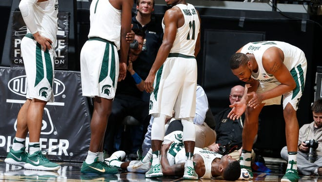 Michigan State's Nick Ward, right, talks to teammate Eron Harris in the moments after Harris injured his knee during Saturday's game at Purdue, as teammates, left to right, Miles Bridges, Joshua Langford and Tum Tum Nairn gather around waiting for Harris to be tended to.