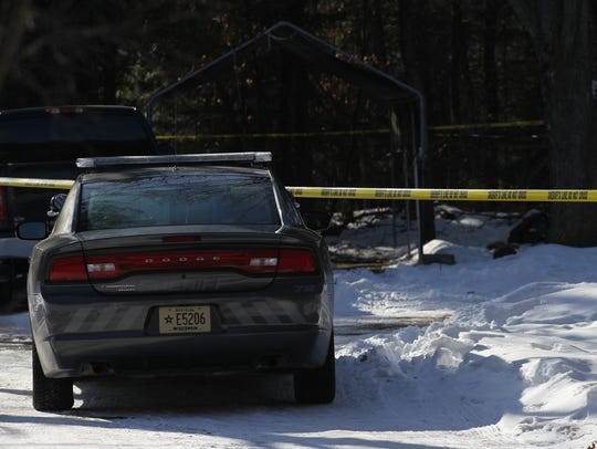 Police tape stretches across the driveway of a town