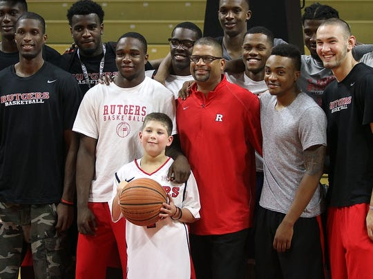 Eleven-year-old Sean Moffitt of North Brunswick poses for photos with coach Eddie Jordan and members of the Scarlet Knights basketball team in 2014.