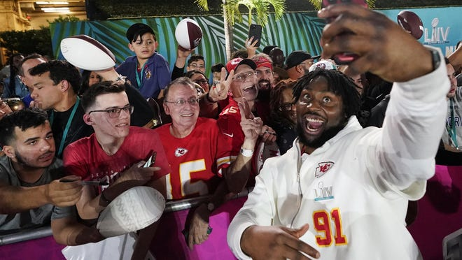 Kansas City Chiefs' Derrick Nnadi poses with fans during Opening Night for the NFL Super Bowl 54 football game Monday, Jan. 27, 2020, at Marlins Park in Miami.