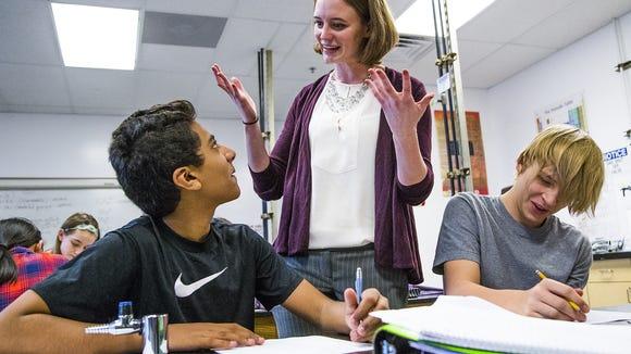 Chemistry teacher Lauren Cooney helps students Benjamin Lalani, left, and Michael Wayrynen, right, both 13, in 8th grade chemistry class, at Basis Scottsdale school, Wednesday, October 7, 2015.