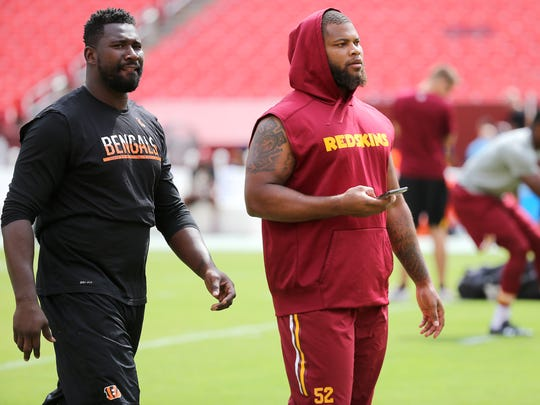 Cincinnati Bengals defensive end Wallace Gilberry (95), left, and his cousin, Washington  linebacker Ryan Anderson, walk together their teams played on Aug. 27, 2017.