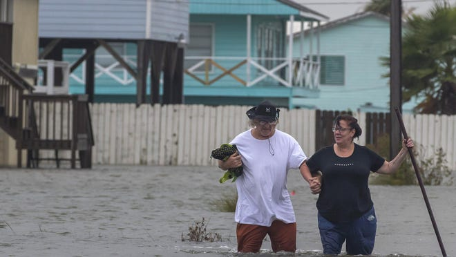 Michael Koudelka and Carol Kelly walk through tidal floodwaters on East Hunter Drive in the unincorporated community of Freddiesville near Bayou Vista on Monday. Tidal surge as well as rain showers from the storm continued to inundate low-lying area around Galveston County.