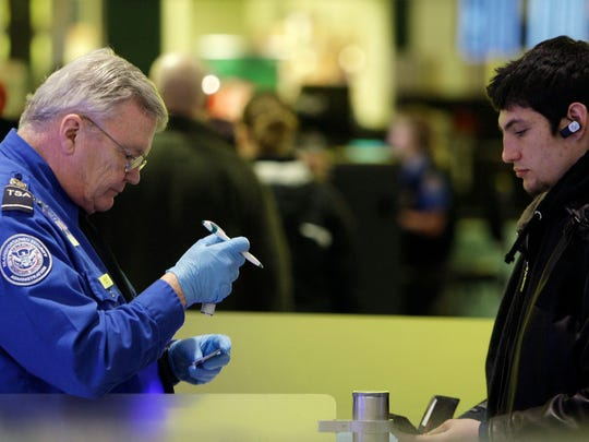 A TSA agent inspects a passenger's ID at Baltimore-Washington International Thurgood Marshall Airport in Linthicum, Md., in 2009.