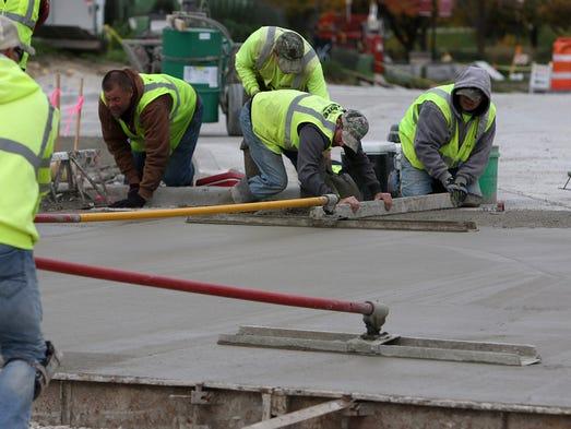Construction crews pour concrete at the intersection