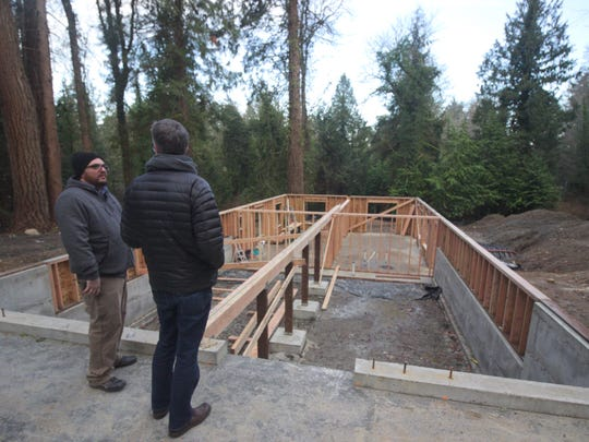 2atara's Andrew Bailey, left, and Craden Henderson look out over the basement of the modular home.