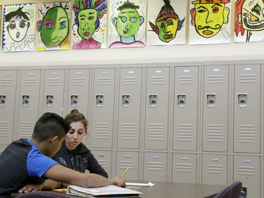 In this April 19, 2016, photo, Laurie Millan, a para-professional and tutor, works with a student during an after school tutoring session at San Francisco International High School, in San Francisco. While some districts in numerous states have discouraged migrant minors from Central America from enrolling in their schools, the school accommodated its youths by rewriting young-adult novels at a basic level to spark the newcomers' interest in reading.