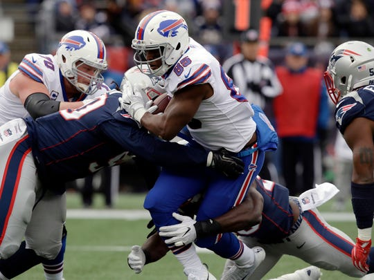Buffalo Bills tight end Charles Clay is tackled by New England Patriots defenders during the first half of an NFL football game, Sunday, Dec. 24, 2017, in Foxborough, Mass.