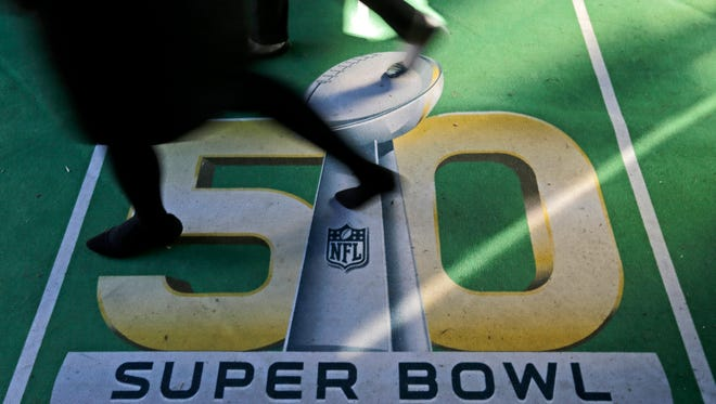 People walk across a Super Bowl 50 logo as they attend an attraction at Super Bowl City Tuesday, Feb. 2, 2016 in San Francisco. The Denver Broncos play the Carolina Panthers in the NFL Super Bowl 50 football game Sunday, Feb. 7, 2015, in Santa Clara, Calif. (AP Photo/Charlie Riedel)