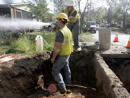 Water maintenance workers, Tyler White, left, and Brandon Bigelow, test the water pressure Thursday, while tapping the water main to create a tap for a new house on Nebraska Street in West Asheville.
