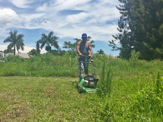 Tony Rodriguez mows a vacant lot he owns at 3313 Jeffcott