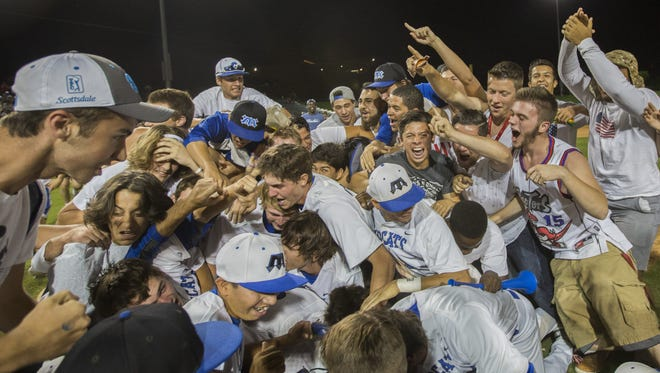 Mesquite players and their student section pile ontop of pitcher Josh Webster (12) after the team wins 5-2 over Liberty capturing the D1 State Championship game in at Tempe Diablo Stadium in Tempe, AZ on May 19, 2015.