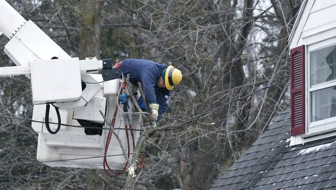 A crew from The United Illuminating Company with headquarters in New Haven, Connecticut, cleans up branches at a home on St. Paul Blvd. in Irondequoit on March 11, 2017.