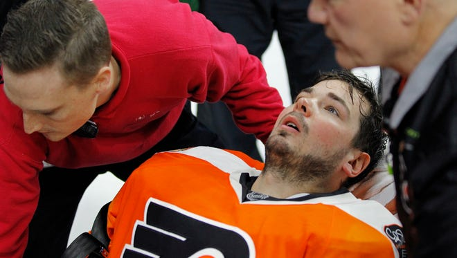 Philadelphia Flyers goalie Michal Neuvirth is taken off the ice on a stretcher after collapsing to the ice early in the first period Saturday night.