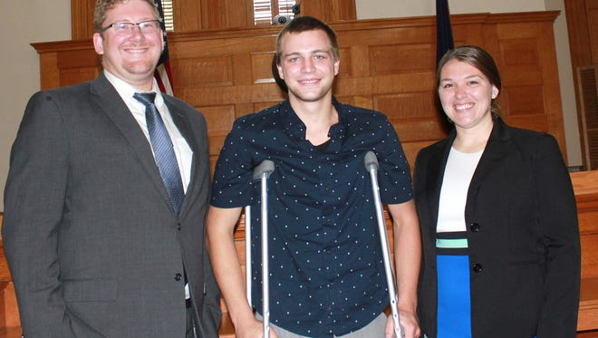 Cameron Cichosz of Howell, center, with Dr. Ryan Keating and Dr. Lauren Azevedo. The doctors were honored at the Barry County Commissioners meeting July 10 for saving the life of Cichosz, whose leg was severed in a boating accident on Gun Lake.