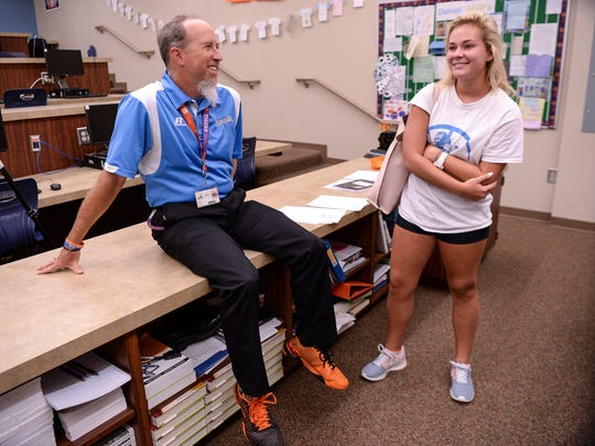 Jon Parker, left, a Computer Science teacher at D.W. Daniel High School in Central, talks with senior Madison Holtzclaw about tennis practice, during school on Tuesday. Parker left a career as a youth pastor to teach and coach tennis.