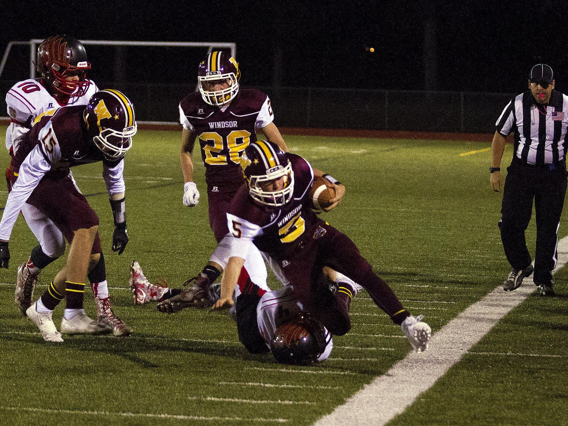 Windsor quarterback Brad Peeples (5) gets taken down at the sideline by Skyline's Josh Balli (4) during first-half action Friday night in Windsor. Michael Bettis/For The Beacon