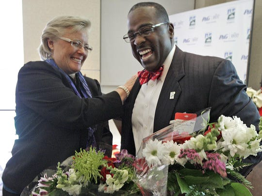 Cincinnati Parks Director Willie Carden Jr. receives a $1 million check for Smale Riverfront Park from Melanie Healey of Procter & Gamble in 2012.