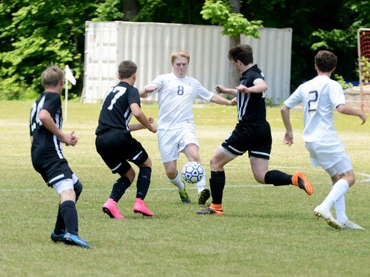 Jackson Christian's Luke Robertson attempts to split two Dyersburg defenders during their Class A-AA Soccer sectional, Saturday afternoon.