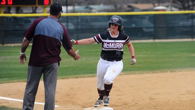 McMurry's Kayla Otis (14) shakes hands with coach David McNally as she rounds third base following her game-winning solo home run in the top of the seventh inning of the War Hawks' 7-6 victory at Hardin-Simmons on Tuesday, Feb. 13, 2018.