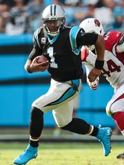 Carolina Panthers quarterback Cam Newton runs with the football against  the Arizona Cardinals defense at Bank of America Stadium on Oct. 30, 2016, in Charlotte.