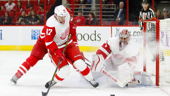Detroit Red Wings goalie Petr Mrazek (34) stops the shot next to teammate defensemen Alexey Marchenko (47) and Carolina Hurricanes forward Jordan Staal (11) during the second period at PNC Arena.