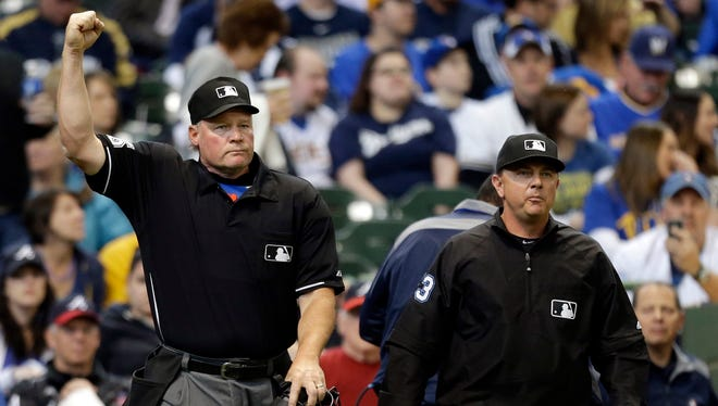 Umpire Ted Barrett, left, signals an out call after listening to the central replay booth in New York.