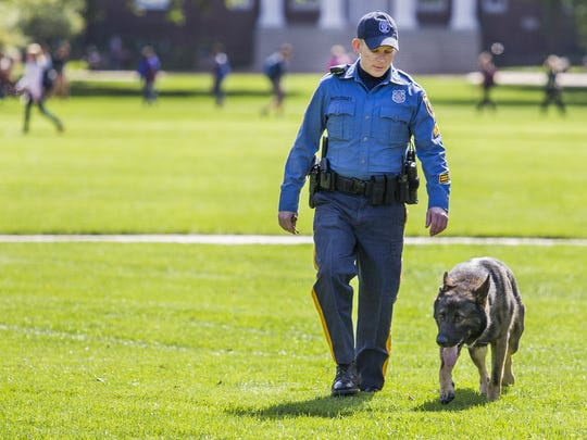 University of Delaware police officer Patrick McCloskey walks with his 6-year-old German shepherd, Scout, along The Green in Newark on Monday afternoon.