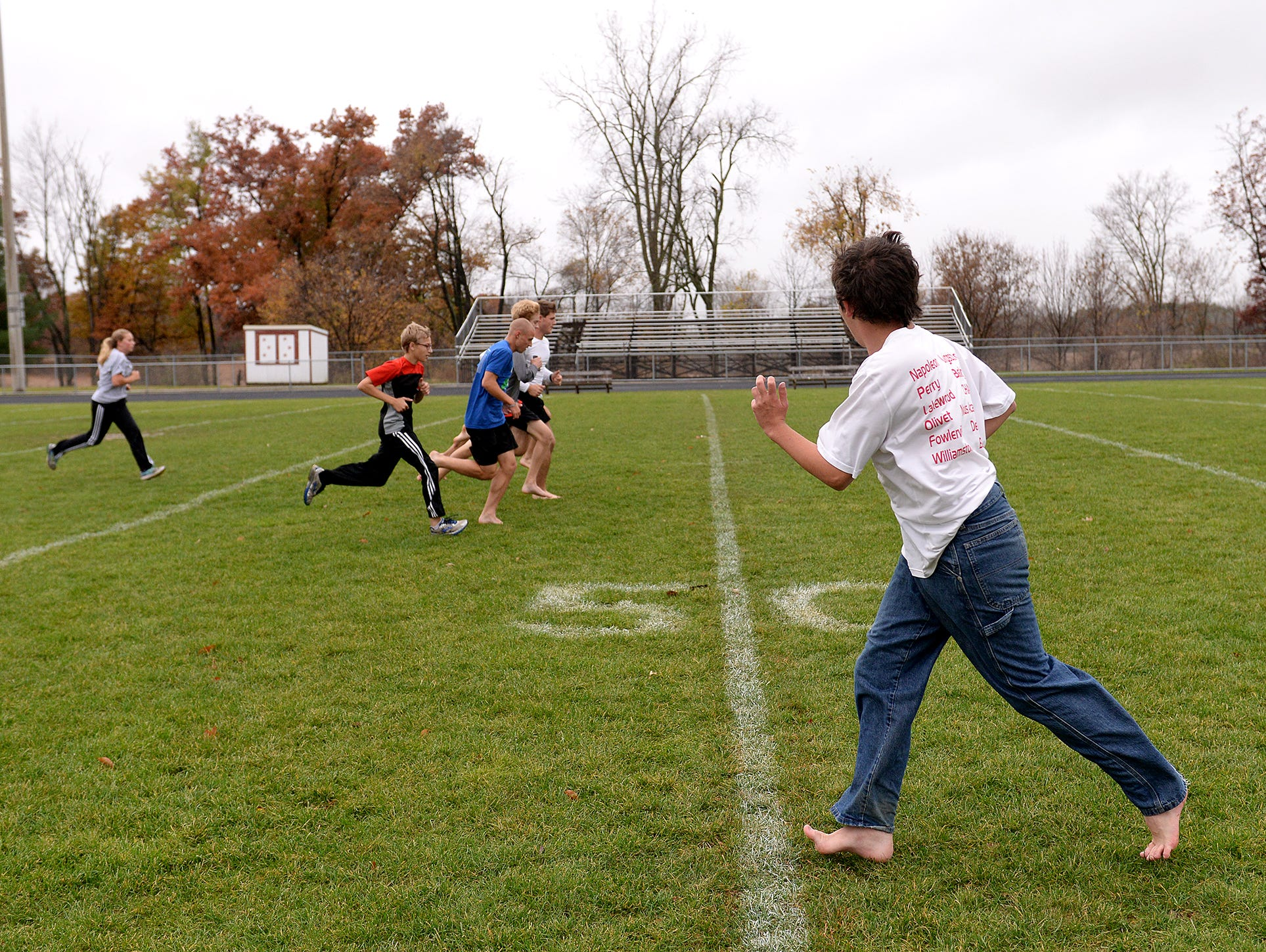 """Ray Latchaw looks over at his teammates on the Laingsburg cross country team Wednesday, October 28, 2015 as they run exercises at Laingsburg High School. Latchaw, a junior, is autistic, but runs, he says, to stay healthy and because he enjoys the """"me time"""" he gets. Ray forgot his running gear at home, so he had to run in jeans."""