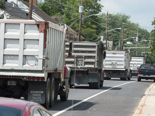 A line of dump trucks travel on West Camden-Wyoming Avenue in Camden on Thursday. The Delaware Department of Transportation's Capital Transportation Program includes funding for a bypass around the congested area.