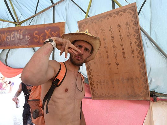 Paolo Briolini learns to spell out his name as he enters the Da Dirty Hands camp dome at Burning Man on Tuesday August 30, 2017. Da Dirty Hands is made up of deaf burners.