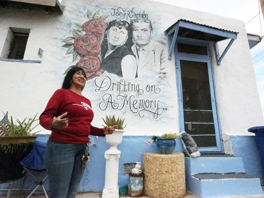 Mannys Silva Rodriguez in front of her home in Chihuahuita. Like many families in this tight-knit community, her family's roots go back generations in Chihuahuita. On the wall is a mural of her parents.