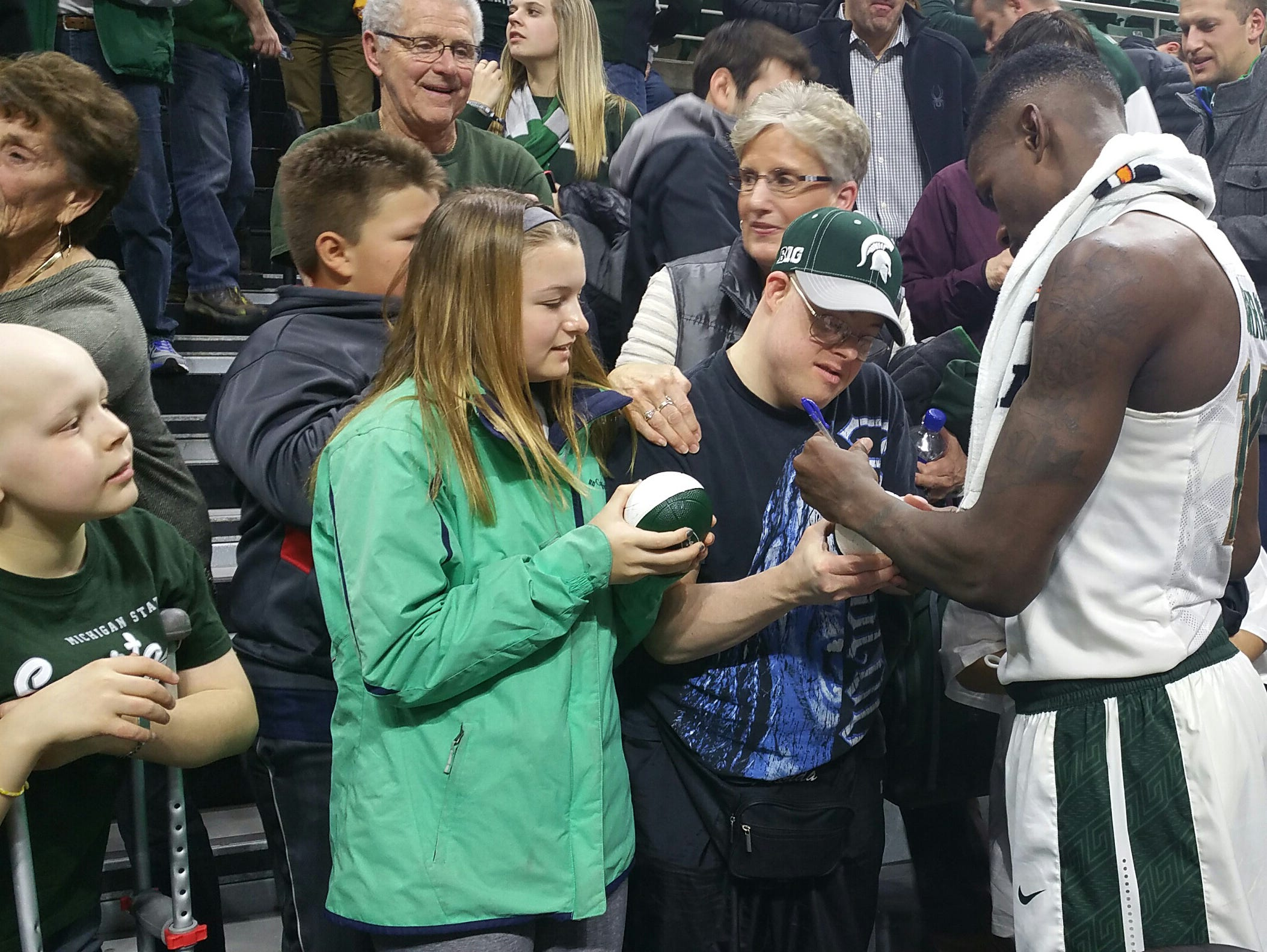MacKale McGuire, far left, waits for MSU basketball player Matt Costello after Thursday's game. MSU guard Eron Harris is pictured at right.