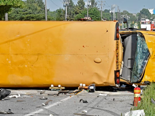 A damaged school bus lies on its side after a collision in East Lampeter Township, Pa., Wednesday, May 17, 2017. Authorities say the school bus flipped on its side in a hit-and-run accident in eastern Pennsylvania, sending more than a dozen people to the hospital, including two students with trauma injuries. Police were seeking a light-colored sedan involved in the crash that sped away.  (Blaine Shahan/LNP via AP)
