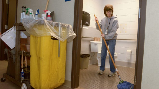 Sara Posvic mops the restroom floor as she does janitorial work at the Rahr-West Art Museum through Holiday House of Manitowoc County's Community Employment Services Program.