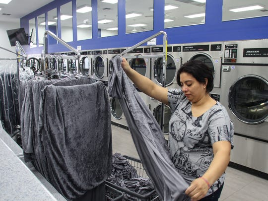 Attendant Laura Jimenez works on a commercial account at Laundry Time in Lakewood.