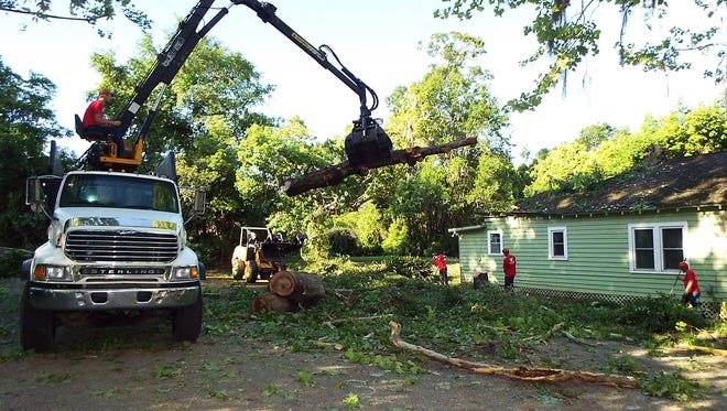 Tree workers remove the last pieces of a tree that fell on a home at 315 W. Call Street on Monday. Two trees on the lot were downed about 10:30 a.m. Monday, as a storm with winds of 40 mph to 60 mph moved through downtown and then spawned a tornado in northeast Tallahassee.