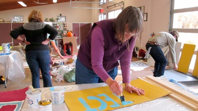 Susan Allen works on a sign for The People's Procession, which starts at noon on Saturday, Jan. 21 at La Capilla, followed by a rally at Gough Park.