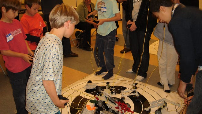 Kids are shown at a past robotics event in this photo from Robotics & Things.